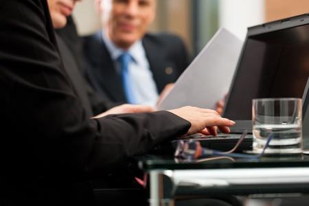 abogado: Negocios - reuni�n del equipo en una oficina con computadora port�til, la mujer frente est� escribiendo