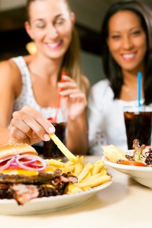Two women - one is African American - eating hamburger and drinking soda in a fast food diner; focus on the meal photo