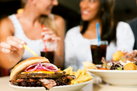unhealthy: Two women - one is African American - eating hamburger and drinking soda in a fast food diner; focus on the meal