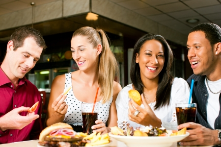friends drinking: Friends - one couple is African American - eating hamburger and drinking soda in a fast food diner; focus on the meal