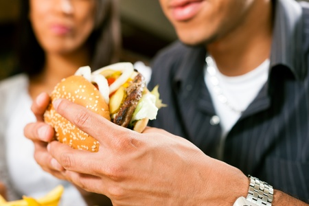 comida chatarra: Hombre feliz (afroamericanos) en un restaurante de comida r�pida de comer una hamburguesa con su novia