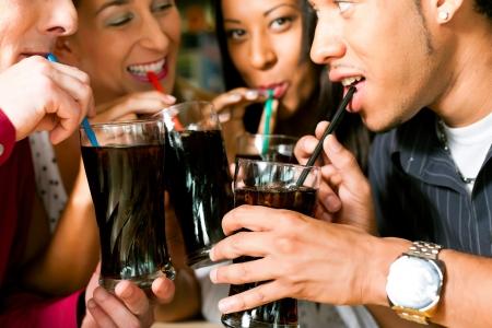 Cuatro amigos de beber refrescos en un bar con pajitas de colores Foto de archivo