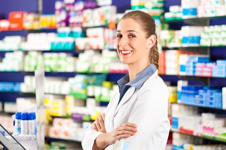 Female pharmacist is standing in her drugstore behind the counter photo