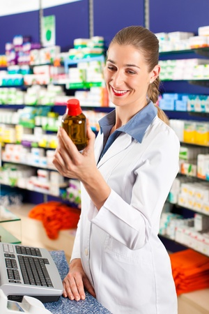 Female pharmacist is standing in her drugstore behind the counter and holds a medicine bottle photo