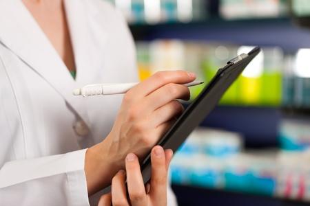 inventario: Mujer farmacéutico o un asistente que está haciendo el inventario o toma de pedidos en la farmacia Foto de archivo