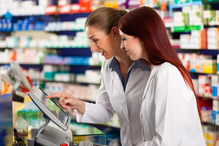 drug store: Pharmacist with female assistant in pharmacy standing at the cashpoint