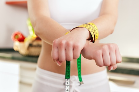 bulimia: Woman handcuffed by a tape measure - symbol for eating disorder