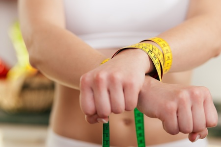 disorder: Woman handcuffed by a tape measure - symbol for eating disorder