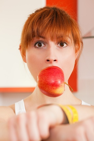 gagged: Woman handcuffed by a tape measure and gagged by an apple - symbol for eating disorder