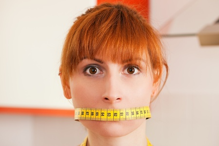 bulimia: Woman gagged by a tape measure - symbol for eating disorder