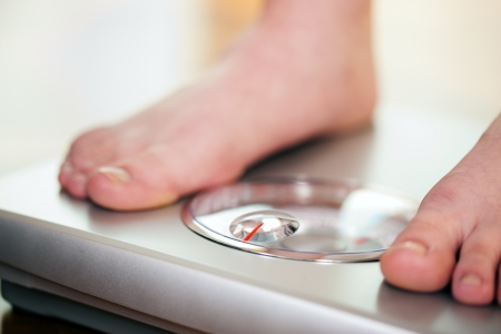 Woman (only feet to be seen) standing on bathroom scale measuring her weight controlling her dieting results  Stock Photo
