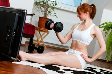 Woman is exercising with weights in her living room watching a fitness video photo