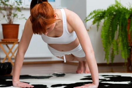 Woman is exercising at home - she is doing push-ups Stock Photo - 11530103