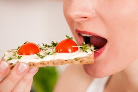 crispbread: Donna, mangiare sano nella sua dieta, avere un pane croccante con crema di formaggio, crescione, e pomodori Archivio Fotografico