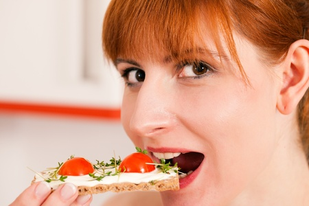 Woman eating healthy in her diet, having a crispbread with cream cheese, cress, and tomatoes  photo