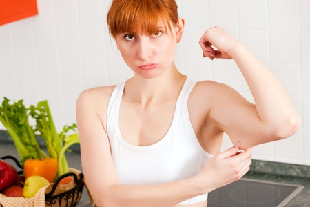 triceps: Woman is checking her triceps and seems to be unpleased