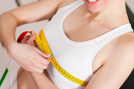 chest women: Thin woman measuring her chest with a tape measure, only the torso to be seen