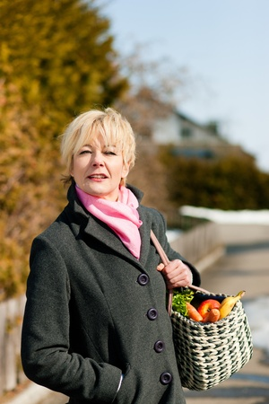 neighborly: Woman with her groceries standing on the street
