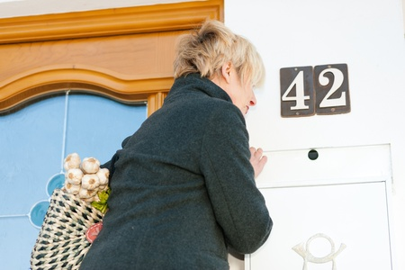 neighbourly: Woman with her groceries looking in her letter box Stock Photo