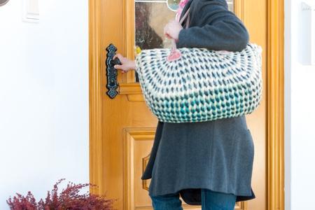 abriendo puerta: Mujer que se casa con su tienda de comestibles y se está abriendo la puerta de entrada