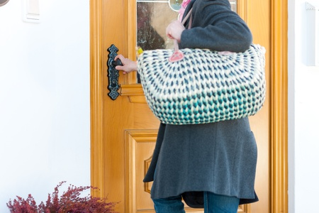 front door: Woman coming home with her groceries and is opening the front door Stock Photo