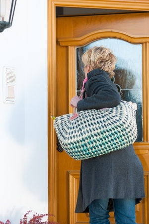 neighbourly: Woman coming home with her groceries and is opening the front door Stock Photo