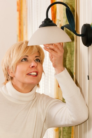 lady with the lamp: Woman changing a light bulb in a lamp hanging in her apartment