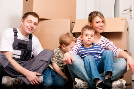 mover: Family moving in their new house. They are sitting in front of a stack of moving boxes being happy. Father is dressed in a way that can also represent a mover  Stock Photo