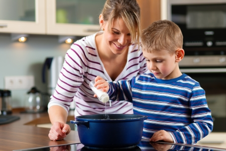 mere cuisine: Cuisine familiale dans leur cuisine - le soleil est de mettre un peu de sel dans l'eau bouillante Banque d'images