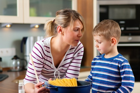 Family cooking in their kitchen - mother and son cooking spaghetti Stock Photo - 11529932