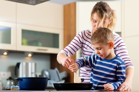 dona de casa: Family cooking in their kitchen - mother and sun cooking spaghetti