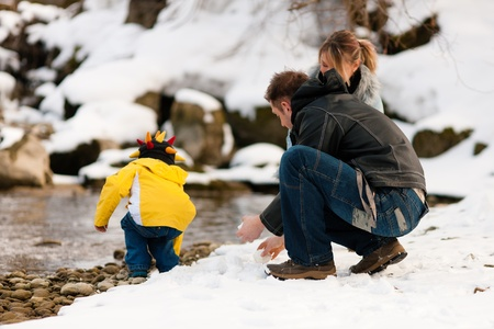 Family - father, mother and son to be seen - on a walk along a riverbank in winter; they are making snowballs   photo