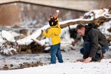 family fight: Family - father and son to be seen - on a walk along a riverbank in winter; the child is throwing a snowball Stock Photo