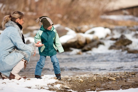 Family - mother and son to be seen - on a walk along a riverbank in winter; the child is throwing a snowball   photo