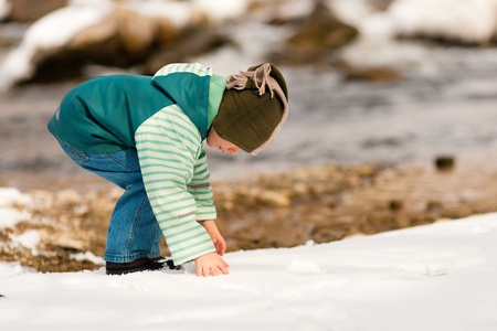 Little boy on a walk along a riverbank in winter; the child is making a snowball photo