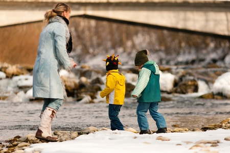 Family - mother and sons to be seen - on a walk along a riverbank in winter; the child is throwing a snowball photo