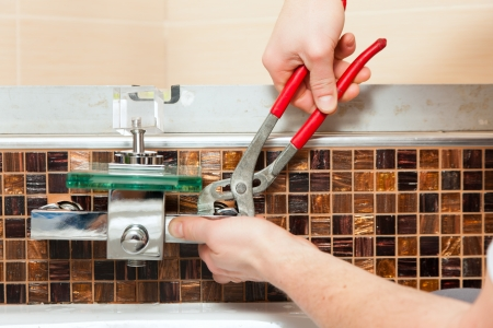 mountings: Plumber installing a mixer tap in a bathroom    Stock Photo