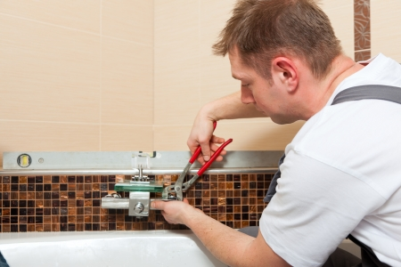 home improvement: Plumber installing a mixer tap in a bathroom    Stock Photo
