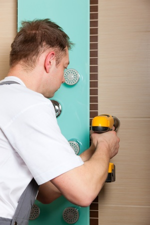 mountings: Plumber installing a mixer tap in a bathroom