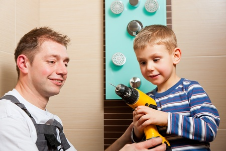 mountings: Plumber installing a mixer tap in a bathroom; he explains it to his son Stock Photo