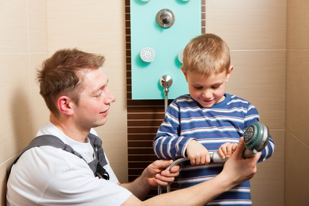 mountings: Father, who is a Plumber, installing a mixer tap in a bathroom; explaining what he does to his son  Stock Photo