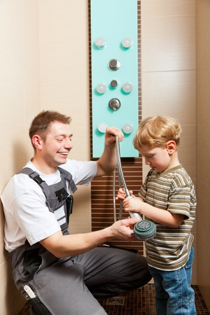 mountings: Plumber installing a mixer tap in a bathroom; he explains it to his son