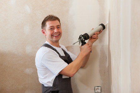 airgun: Worker grouts with silicone; it is presumably a new house