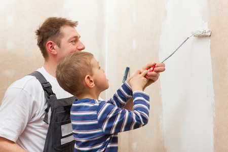 Father and son painting a wall in their home, they presumably do it in the course of moving in photo