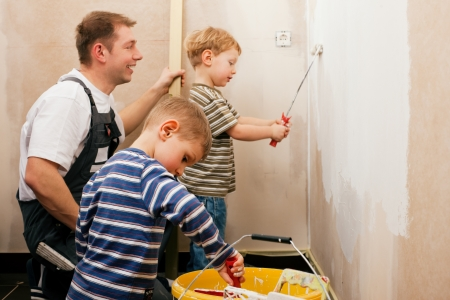 Father and sons painting a wall in their home, since the wall is still raw they presumably do it in the course of moving in  photo