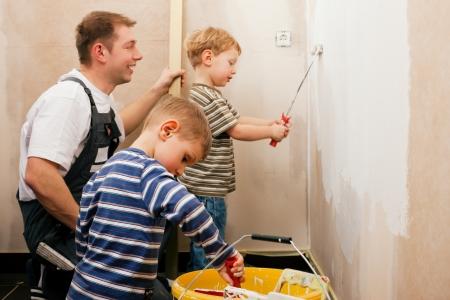 work together: Vader en zonen schilderen van een muur in hun huis, want de muur is nog steeds rauw ze vermoedelijk het te doen in de loop van bewegen in