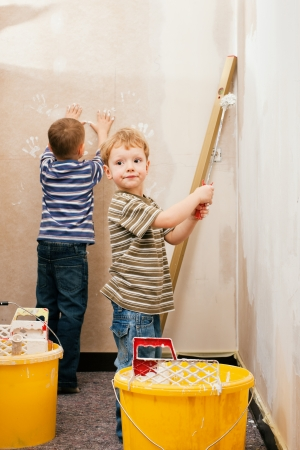relocating: Family concept - two boy painting a wall in their home, one is making hand prints the other one using a paint roll  Stock Photo
