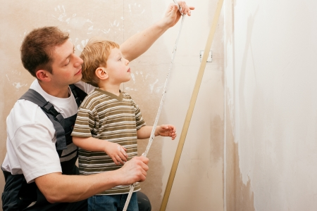walling: Father and son measuring a dry wall in their home with a folding rule and a bubble level