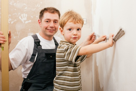 Father and son measuring a dry wall in their home with a folding rule and a bubble level  photo