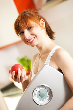 kitchen scale: Thin and beautiful woman standing in her kitchen with an apple and a weight scale in her hand, symbol for loosing weight, diet, and healthy nutrition, in the background there is a fruit bowl